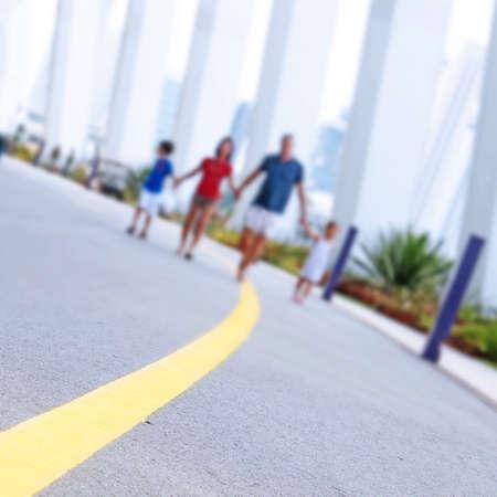 crossing street: happy family walking in the park