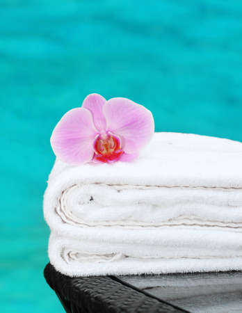 room service: clean towel with orchid poolside Stock Photo