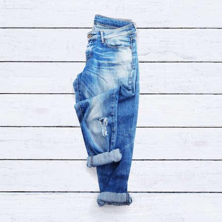 白い木製の背景にジーンズ