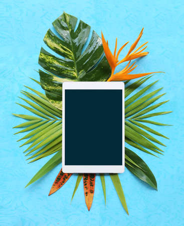 tropical plants with tablet on blue background