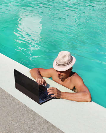 beautiful man with laptop by the pool