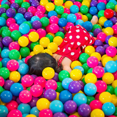 playpen: Little Girls playing lying in colorful balls park playground