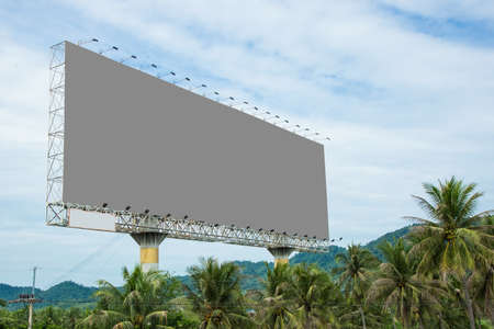 mountainous: Big grey billboard on highway. Has a mountainous backdrop and the foreground or coconut. Stock Photo