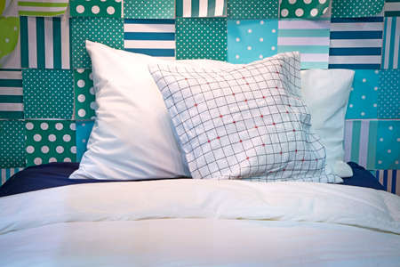 queen bed: Two pillows on the bed with colored paper taped to the wall.