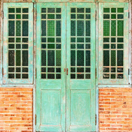 redbrick: Old door green (vintage style) red-brick walls. Stock Photo