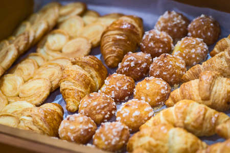 Box of breakfast pastries. Two wooden trays, flaky croissants, and apple danishes.