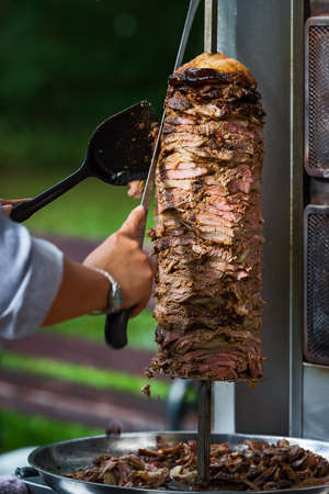 An arm moving to cut the kebab meat Stockfoto