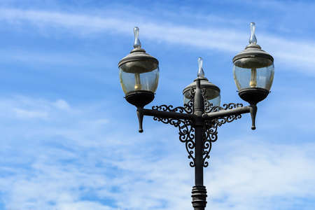 vintage lighting pole with twin double lamp lantern on background of blue sky.