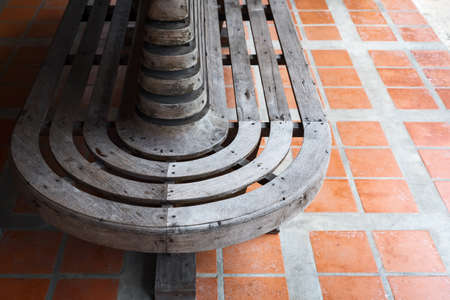A vintage wooden bench curved can sit in all directions.