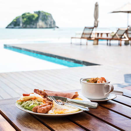The English breakfast consists of fried eggs, bacon, sausage, and green salad, And Thai rice soup with shrimps With a beach backdrop at Thailand