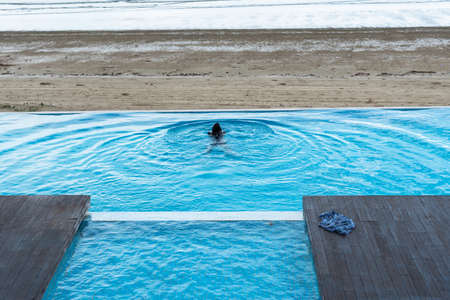 The waves at the surface of the water in the outdoor pool and the beach by the sea have children splashing in the pool. 版權商用圖片