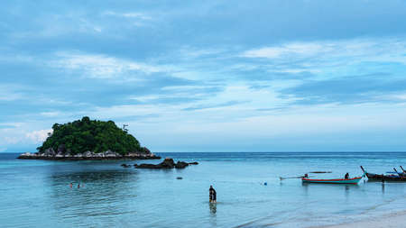Koh Lipe, Andaman Sea, Thailand, 18 September 2019: Tourists take a walk along the beach and swim at Koh Lipe, beautiful beaches and sea. There is a long tail boat of fishermen at Koh Lipe, Thailand. 版權商用圖片