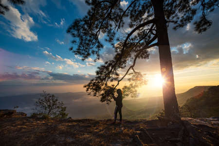 The silhouette of a female traveler is excited by the sunset view at Phu Kradueng, Loei Province, Thailand.