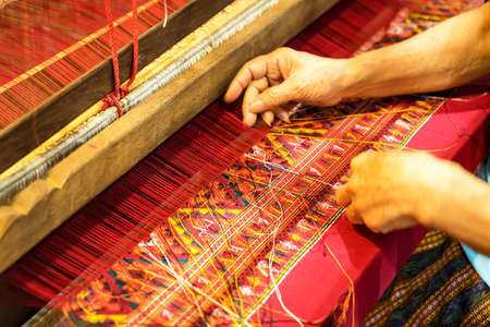 Close up Hand insert silk thread to cloth there setting in wooden weaving loom. Old tradition textile work in Thailand.