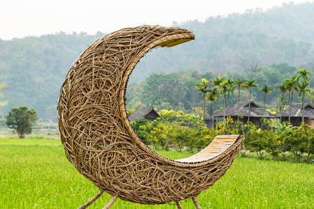 A bench made of half-moon rattan in a green paddy field with a mountain backdrop and a village.