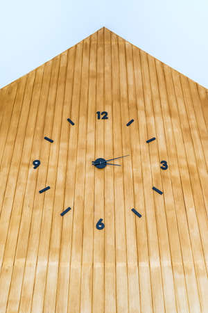 Analog clock with hands and numbers in black on brown wood wall. 版權商用圖片