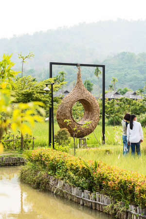 The swings are made of rattan and straw, with a backdrop of mountains and rural villages. 版權商用圖片