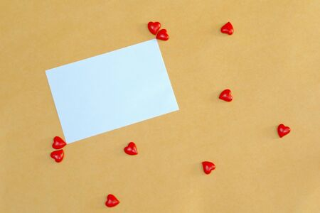 White paper note and mini red hearts on brown table. Valentines, Birthday, Mother or Father day. Free space for any text design. Flat lay.