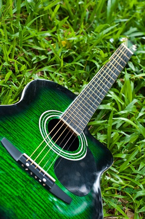 country music: acoustic guitar on green grass yard