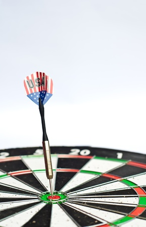 dart board: dart in center of dartboard with isolated white background