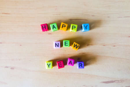 Happy New Year of colorful beads arrange on a wooden table background.