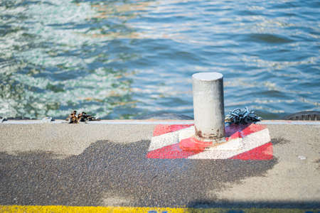 Bollard on the harbor edge by the river around by white and red frame markings