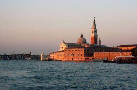 The setting sun casts an orange glow on the buildings of the venetian island of La Giudecca