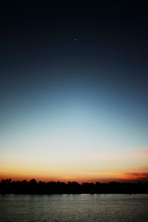 Nightfall with crescent moon over a river