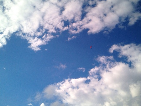 Red paraglider high up amid clouds against the blue sky