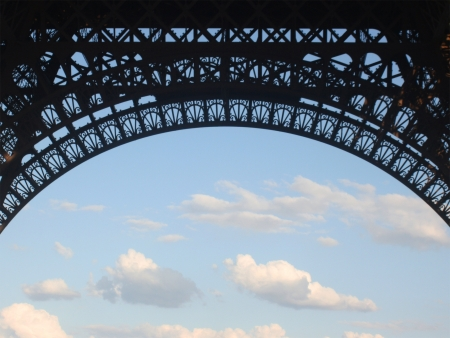 Eiffel Tower arch against blue sky and clouds