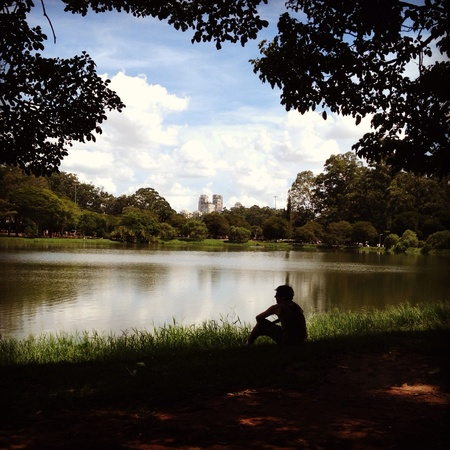 Sitting man silhouetted against lake water
