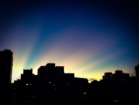 City skyline against sun rays at nightfall Stock Photo