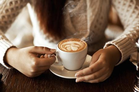 tazas de cafe: manos de la mujer con el café con leche en una mesa de madera Foto de archivo