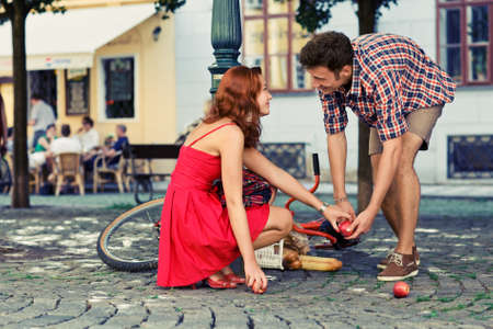 man fell down from the bicycle and woman help him to collect products Stock Photo
