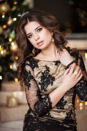 female christmas: Christmas Mood. Beautiful woman model. Makeup. Healthy long hair style. Elegant lady in luxury fgolden dress fover christmas tree lights background. happy new year. Stock Photo