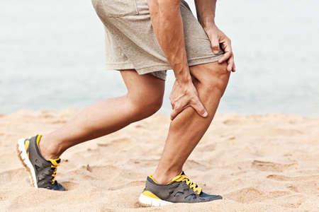 근육 부상. 염좌 허벅지 근육을 가진 남자. 잡아 당기거나 해변에서 조깅하면서 그들을 긴장 후 그의 허벅지 근육을 쥐고 스포츠 반바지 선수.