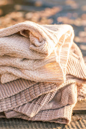 tejido de lana: Pila de ropa de invierno de punto en el fondo de madera, suéteres, prendas de punto
