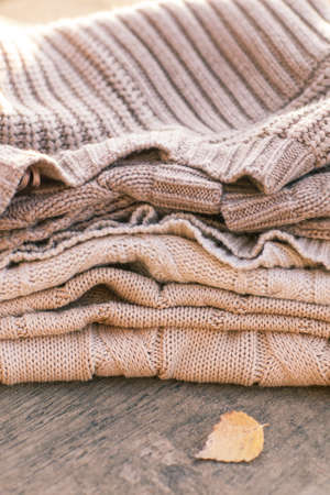 knitwear: Pile of knitted winter clothes on wooden background, sweaters, knitwear