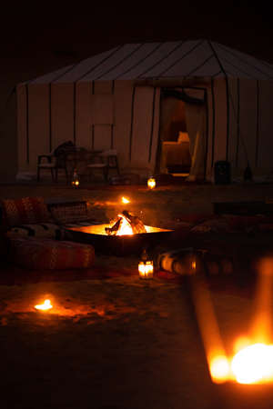 Evening glamping tents in Sahara desert in Morocco. Luxurious camping resort in nature dunes, glamping vacation in Africa.