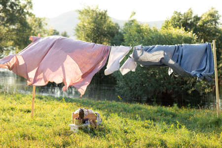 Pink and blue bedding sheet on forest background under the bright warm sun. Clean bed sheet hanging on clothesline at backyard. Hygiene sleeping ware concept.