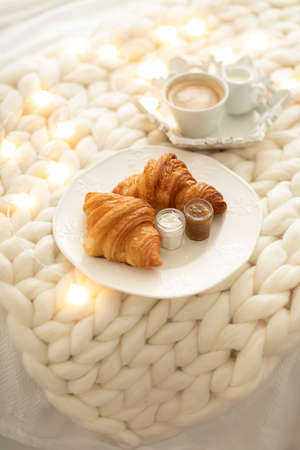 Fresh croissants with jams and americano with milk on knitted white wool blanket and luminous garlands. Cozy winter morning at home. Scandinavian bedroom.