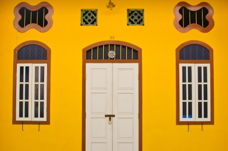 White door and window with yellow wall