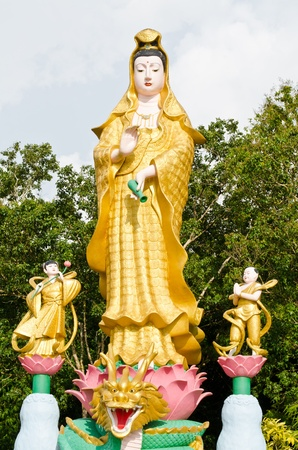 Golden statue of Guan Yin with children in temple at Phan Nga, Thailand  Stock Photo