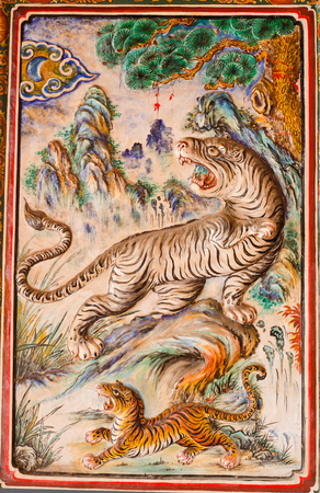 Ancient tigers design on wall background in chinese temple at Phuket Stock Photo