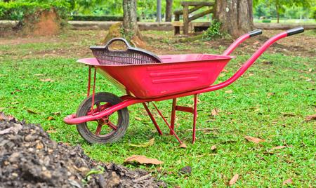 Red wheelbarrow in a garden Stock Photo