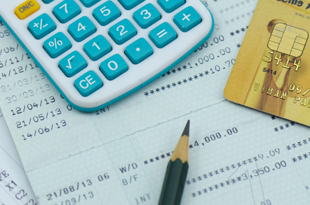 close up bank statement with calculator and pencil photo