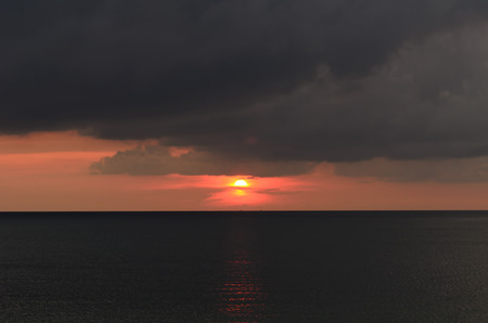 Sunset with dark cloudy in the black ocean, summer season Stock Photo