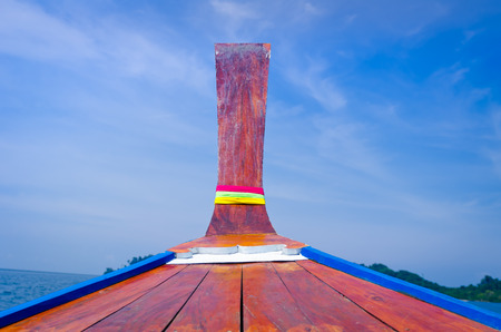Head of wooden long tailed boat with blue sky
