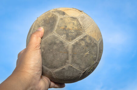 old soccer ball in hand and blue sky  photo