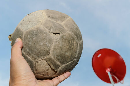 old soccer ball in hand and red satellite background  photo